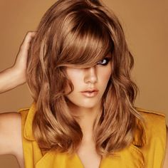 This modern balayage technique from DCI Education melts beautiful gold tones into sun-lightened ends for a strong 1970s vibe that complements the multi-layered, mid-length cut.