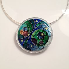 Large cloisonne enamel pendant in an innovative lasercut lucite and silver setting.