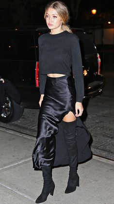"If there was such a thing as ""casual-glam,"" it would look like Gigi Hadid's all-black ensemble here, which mixes low-key silhouettes with high-end fabrics (her cashmere Everlane sweater, satin slit skirt and thigh-high stretch leather Stuart Weitzman boots)."