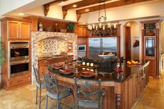 An enlarged island takes up the center of this sophisticated mediterranean kitchen with a bar on the end. A brick surround showcases the backsplash and cooking area to highlight it as the most important part of this family's kitchen.