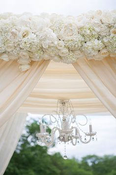 Lush white roses, peonies and hydrangeas are used to decorate this beautiful chuppah.
