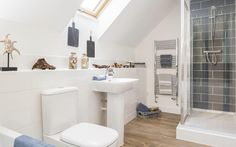 Georgeous interior designed loft room ensuite shower and bath room - modern and less cheesey version of the seaside theme - love the dark grey/blue tiles in the shower and a wood floor.  David Wilson Homes.