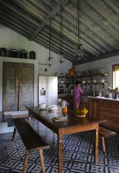 Painted cupboard. Flooring. Pendant lamps. Table and bench. Corrugated tin ceiling.