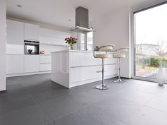 White kitchen with metal elements on slate gray floor Slat . White Glossy Kitchen, All White Kitchen, Grey Flooring, Kitchen Flooring, Interior Design Living Room, Living Room Decor, Contemporary Kitchen Design, Küchen Design, Home Remodeling