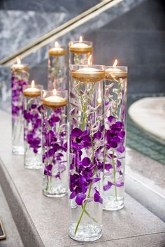 Purple Wedding Flowers Glass Vases With Purple Orchids and Floating Candles - Wedding Reception Flowers, Purple Wedding Flowers, Purple Orchids, Floral Wedding, Reception Ideas, Trendy Wedding, Wedding Ideas, Purple Wedding Flower Arrangements, Purple Glass