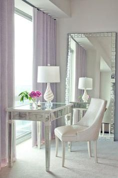 An all white chic bedroom with a mirrored desk and mirror and the addition of soft lavender draperies - fabulous!