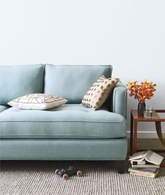Blue sofa in a living room. I'd like the color for my home, but not the shape of the couch arms. It looks uncomfortable.