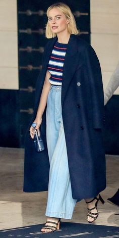 Margot Robbie demonstrated a chic everyday look, wearing wide-leg jeans, a stripe top, navy coat, and strappy heels.