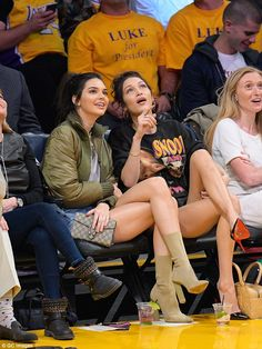 Making a spectacle: Kendall Jenner (left) and Bella Hadid (right) showed off their long legs as took front row seats at the Los Angeles Lakers game at the Staples Center