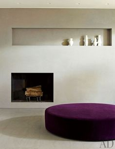 In a home in New Canaan, Connecticut, an ottoman by B&B Italia sits beside a minimalist fireplace.: