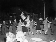 Men and women dance the conga around a bonfire in East Acton, London on the evening of VE Day. VE DAY CELEBRATIONS IN LONDON, ENGLAND, 8 MAY 1945 (Imperial War Museum)
