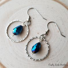 Round silvertone drop earrings with blue briolette accent bead