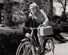 Jan Sterling rides a bike. And eats an apple. And carries her...