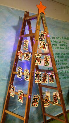 Avet de nadal amb escala, llums de colors i fotografies de nens i nenes.