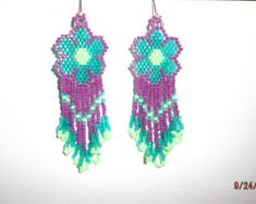 These Native Grey Wolf are custom made by Elaine. They are made in Grey,Teal, Hot Pink and Black Delica Beads. It has Gold ear wires, can be changed to post or clips. Earrings are 3 in. long. If you have any Questions for would another Color Please email me.   Thanks for looking.