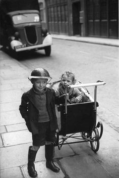 London. 1940 (hey, the streets are a rough place, you can't even take your kid brother for a stroll without your helmet & rubber boots )