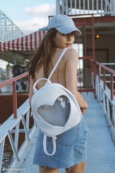 A faux leather backpack featuring a clear heart shape, a high-polish zipper top, dual shoulder straps with adjustable buckles, and a top handle.