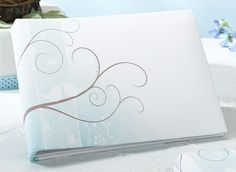 Love Birds Wedding Guest Book covered in white satin. The left side of the cover has a subtle blue floral designwith leaf and brach details. There are also brown swirling branches with two white love birds perched on it. Inexpensive Wedding Favors, Wedding Favours, Wedding Themes, Wedding Reception, Wedding Invitations, Wedding Ideas, Wedding Napkins, Wedding Decor, Wedding Planning