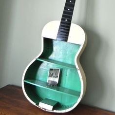 oh snap! using a damaged, old guitar for shelving? way cool.