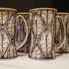 A phalanx of mugs for #mugshotmonday Working on a large order right now but hoping to get some pieces into my online shop soon too! . . #apottersworkisneverdone #mugsmugsmugs #ash #mountainash #leafpattern #canadianclay #canadianceramics #honey #indigo #bone #pottery #designinspiration #tableware #tablewaredesign #makersmovement #ceramics #ceramique #poterie #canadianstyle