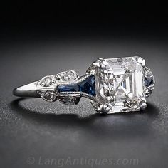 A glorious and glistening classic square emerald-cut - aka Asscher-cut - diamond is the star attraction of this showstopping engagement ring, crafted in platinum and accented with calibre-cut faceted sapphires - circa 1930s. A ravishing, rare and original Art Deco engagement ring for a lucky lady of the same qualities.