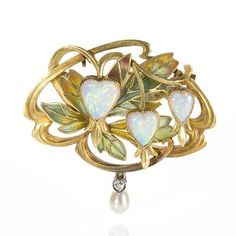 """A French Art Nouveau 18 karat gold brooch with 3 heart shaped white opals accented by a freshwater pearl and diamond drop by Gaston Laffitte. The heart shaped opals represent flowers and the leaves are made of """"plique-à-jour"""" enamel. Gaston Laffitte, was an Art Nouveau jeweler proficient with plique-à-jour enamel techniques. He exhibited regularly at the Paris Salons. Circa 1900."""