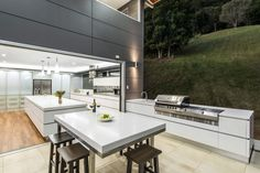 This modern outdoor kitchen appears as an extension of the interior kitchen with the same white cabinets and stainless steel appliances.