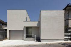 位於島根縣的這個住宅,是建築師山根秀明的設計作品,考量附近緊鄰的建物關係,這個基於隱私外觀減少開窗,內部以中庭形式引進光亮和自然風流動的住家,內外以樹脂塗料加上光觸媒作防護,成為極好維護的簡約住宅。  via 有限会社アイエムユウ建築設計事務所