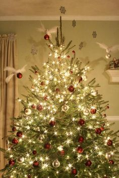 LOVE this tree, white lights, red ornaments. CLassic. ALso, love the snowflakes suspended with fishing line from the ceiling! beautiful!