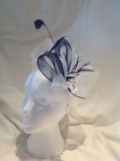 The Ruby is a medium fascinator with a diamond white crinoline base and head band loops of onyx black and diamond white crinoline surround a white butterfly centre piece decorated with diamante's and matching feathers. $85 AUD.