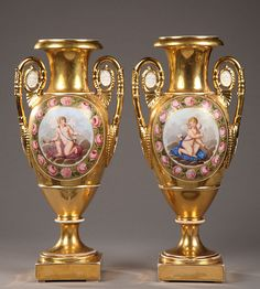 Important pair of gilt porcelain vases with handles decorated with female antique masks inside of medallions. The body of the vases is decorated with wide polychrome cartouche representing o