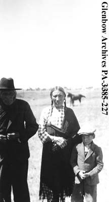 Crooked Meat Strings, Mrs. McMaster, and child, Blackfoot (Siksika) reserve, Alberta. Date: 1938 or 1939. Photographer/Illustrator: Hanks, Jane and Lucien.