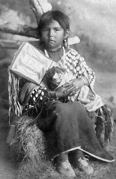 Little Thunder Hawk, a Crow girl, holds her doll in a craddleboard in this 1888 photo taken by Orlando S. Goff.