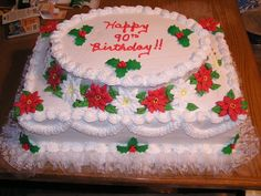 Poinsettia Cake - This was made for a Christmas/Birthday celebration.  It's a 12x18 two layer cake with an oval on top.  Around the sides of the oval are red and white royal icing poinsettias.  The bottom border and top of the oval are accented with gumpaste holly.