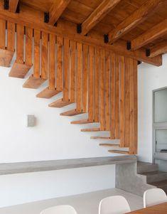 Interno rustico e industriale con la scala creata in cemento, per i suoi primi gradini, e legno massello per la parte superiore che sembra sospesa al soffitto