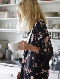 Kimono gown with pretty pink flowers is a perfect wear for a fresh morning cup of coffee.  Looks attractive in the clean white kitchen.