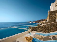 Relax in your private pool at the Hotel Cavo Tagoo overlooking the bright blue Aegean Sea, nestled in the cliffs of Mykonos, Greece.