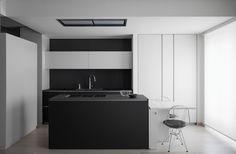 reforma cocina abierta con isla para fregadero y muebles color carbón, módulo empotrado y barra blancos, suelo parqué.