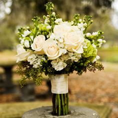 Cream roses accented with lush greenery give off a rustic vibe.