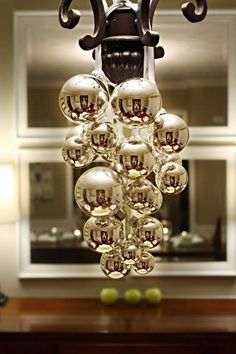 Hang Christmas balls from your chandelier with pretty ribbon.  Love the reflection in the silver.