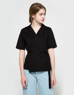From Just Female, a wrap around top in Black. Featuring a slim peak lapel, short sleeve, centered back seam, darts at chest, and wrap around construction with coordinating attached sash.