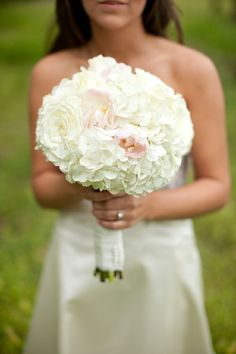 Stunning white bouquet with hints of pink featured in a real wedding on Style Me Pretty. This bouquet is made up of peonies, white hydrangeas and roses.