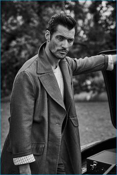 David Gandy poses for a black & white image, donning an oversized coat.