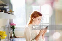 Stockfoto : woman texting on mobile in kitchen
