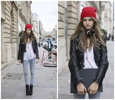 Cara Delevingne wearing a red beanie hat, black leather jacket, light denim skinny jeans and beats head phones for a casual look