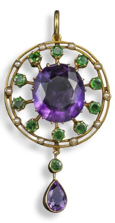 An early 20th century suffragette pendant. Of circular form and set with a large central oval-shaped amethyst within a border of demantoid garnets and seed pearls. Suspending a further pear-shaped amethyst and circular-cut demantoid garnet in yellow gold. 6cm long. #Suffragette #Edwardian #pendant