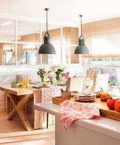 Cocina office con mesa de comedor de madera, lámparas de metal industriales, tabique acristalado y mucha luz