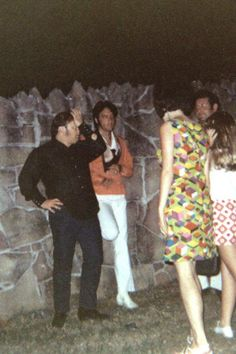 {*Elvis with the white pants on leaning on the wall of Graceland with Joe Esposito talking to some Lucky fans*}
