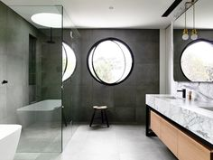 clean gray tiles + circular window + natural stone lavatory counter top with wood cabinetry + glass shower partition ~via contemporist Wolseley Residence Architecture, Interiors and Builder: mckimm Mural: Lucas Grogan Engineer: BDD Engineering Landscaping: Gills Landscaping Photography: Derek Swalwell