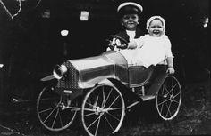 Two children in a pedal car, near Taroom